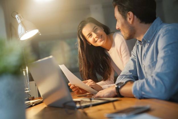 Beau couple à la recherche d'un ordinateur partagé à la maison