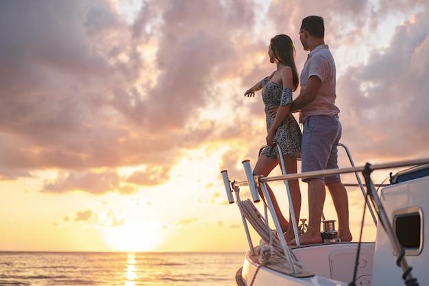 Beau couple regardant le coucher du soleil depuis le yacht