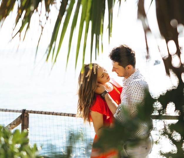 Un beau couple regardant la mer par une journée ensoleillée et embrassant et embrassant