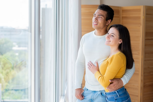 Beau couple regardant par la fenêtre
