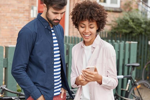 Beau couple regarder une vidéo sur un gadget à l'extérieur