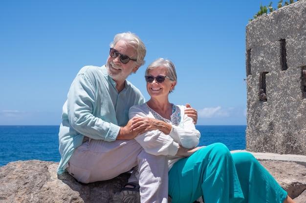 Beau couple de retraités profitant de vacances à la mer, assis et embrassé, regardant ailleurs. horizon bleu au-dessus de l'eau