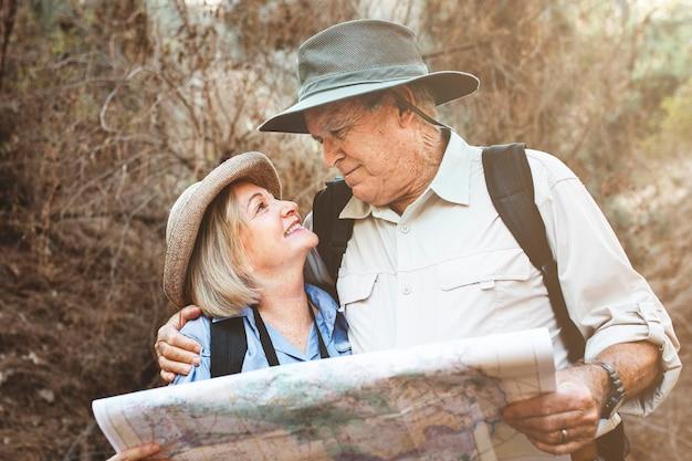 Beau couple de retraités utilisant une carte pour rechercher la direction