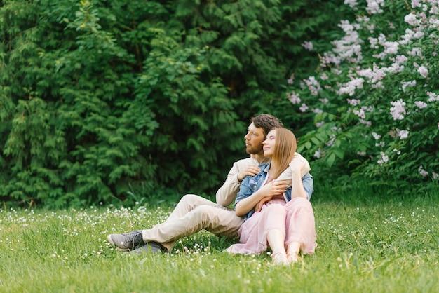 Beau couple romantique assis dans le parc au printemps sur l'herbe près d'un buisson de lilas en fleurs