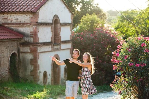 Beau couple romantique homme et femme jeunes adultes se promenant dans la vieille ville fleurie
