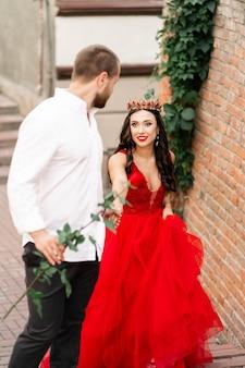 Beau couple romantique. jolie jeune femme en robe rouge et couronne avec bel homme en chemise blanche avec rose rouge marchant dans la rue. bonne saint valentin. concept de grossesse et de mariage.