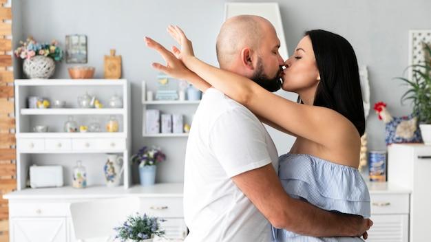 Beau couple s'embrassant à la maison