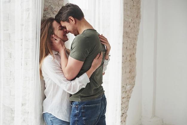 Beau couple s'embrassant et s'amusant près de la fenêtre de leur nouvelle maison.