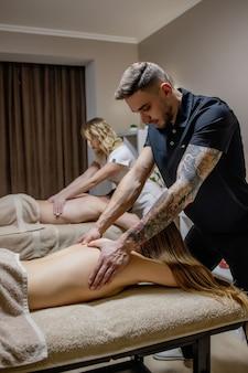 Beau couple se faisant masser le dos, spa de week-end pour couple. belle femme et homme se détend pendant le massage du dos.