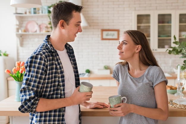 Beau couple se penchant sur la table et savourant du thé