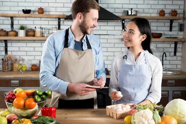 Beau couple se regardant tandis que l'homme écrit la recette dans le journal