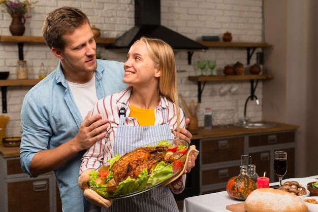 Beau couple se regardant et tenant la dinde de thanksgiving