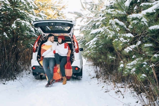 Beau couple souriant assis dans le coffre de la voiture dans la forêt d'hiver