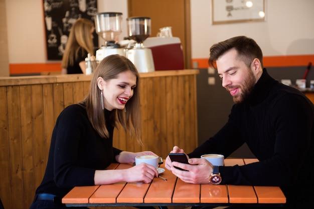 Beau, couple souriant, dans, café, utilisation, téléphone