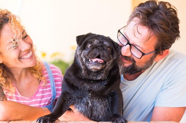 Beau couple souriant et embrassant leur vieux chien carlin noir extérieur en terrasse amour et famille