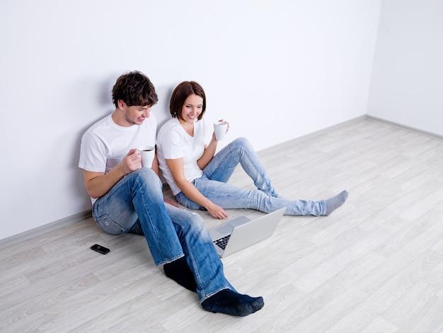 Beau couple souriant avec ordinateur portable dans la salle vide