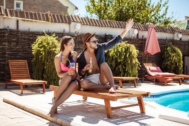 Beau couple souriant, parlant, buvant des cocktails, assis près de la piscine