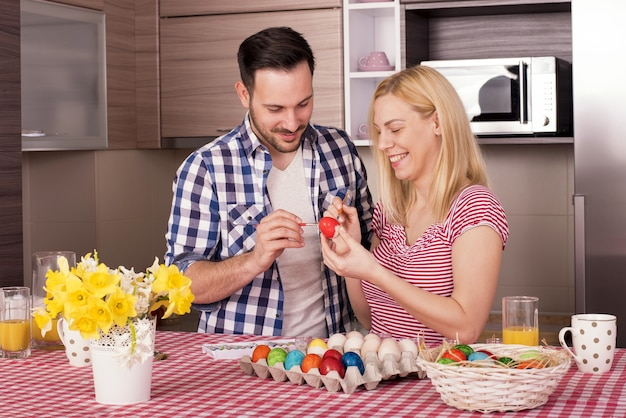 Beau couple souriant et peignant les oeufs de pâques