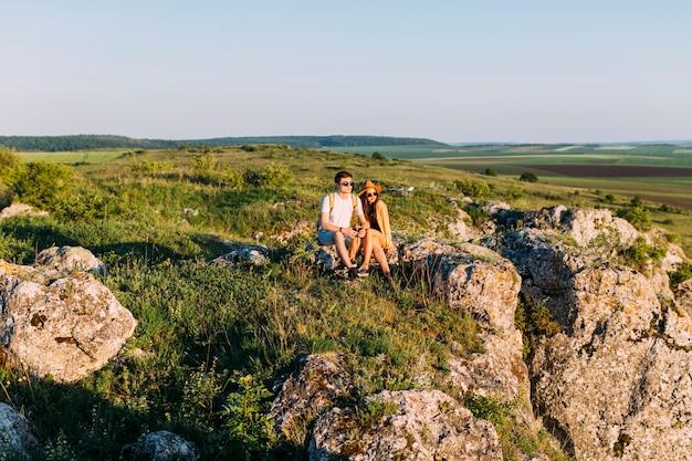 Beau couple souriant relaxant sur le rocher après la randonnée