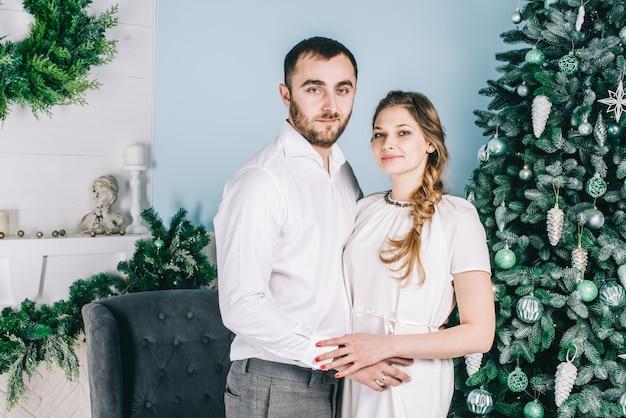 Beau couple souriant romantique se trouve près de l'arbre de noël