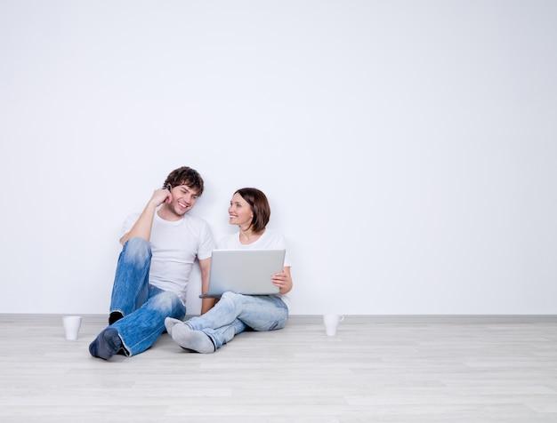 Beau couple souriant se détendre dans la salle vide avec ordinateur portable