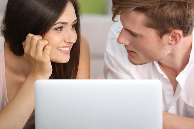 Beau couple surfant sur internet sur ordinateur portable à la maison