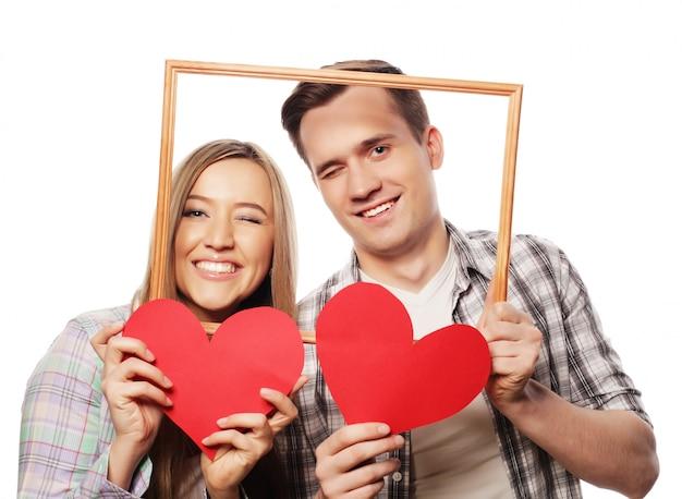 Beau couple tenant le cadre et les coeurs rouges