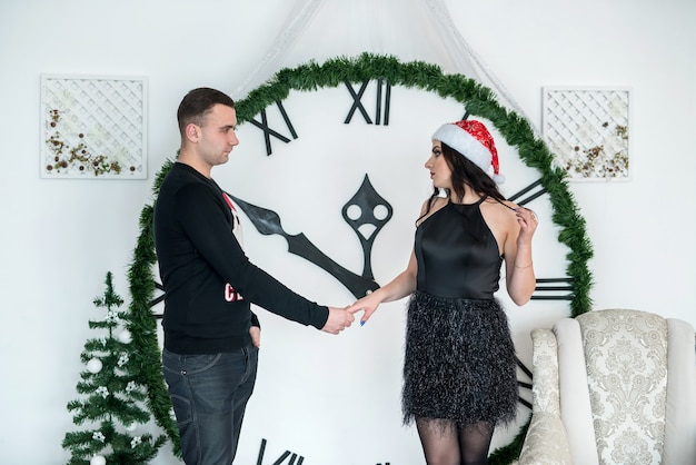 Beau couple tenant leurs mains contre grande horloge