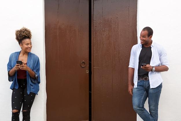 Beau couple tenant des téléphones cellulaires et debout par la porte
