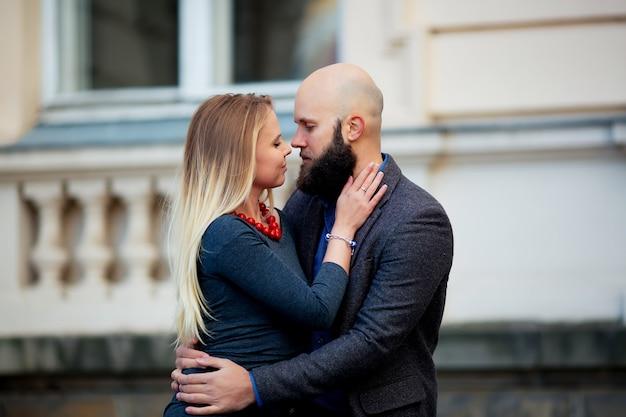Un beau couple tendre élégant de jeune femme et homme senior avec longue barbe noire embrassant près les uns des autres en plein air au printemps journée ensoleillée