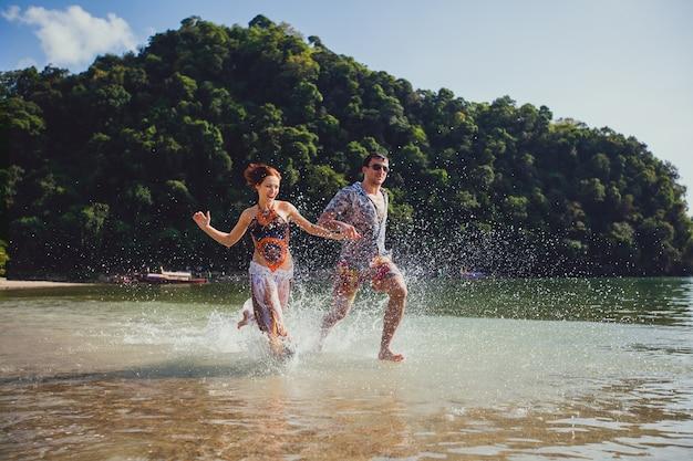 Beau couple de touristes, tenant par la main, courant le long de la plage