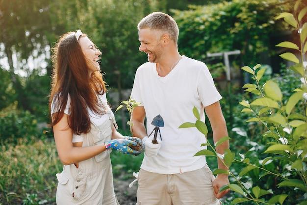 Beau couple travaille dans un jardin