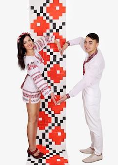 Beau couple ukrainien vêtu de costumes traditionnels en forme de coeur mains