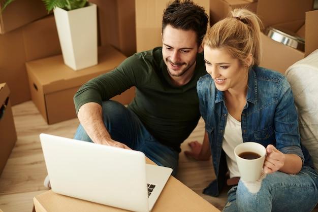 Beau couple utilisant un ordinateur portable parmi des cartons