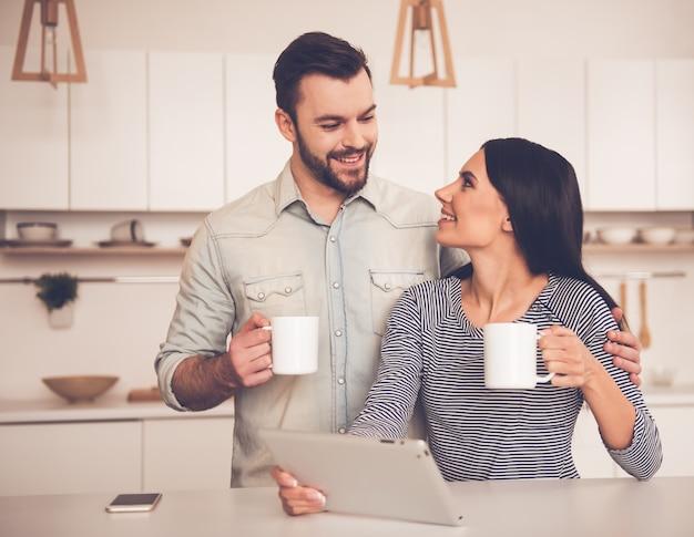Beau couple utilise une tablette numérique, tenant des tasses.