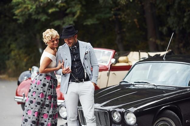 Beau couple en vêtements à l'ancienne près de voiture rétro avec forêt en arrière-plan.