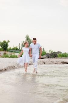 Beau couple en vêtements blancs marchant sur la mer
