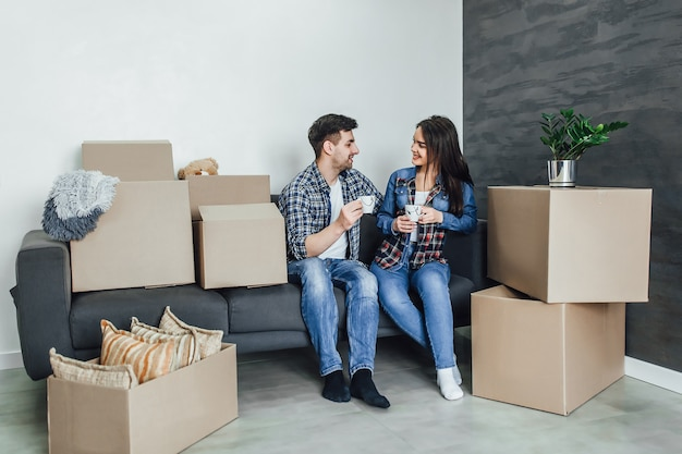 Un beau couple en vêtements décontractés discute du plan de leur nouvelle maison et sourit en étant allongé sur le canapé près des boîtes de déménagement