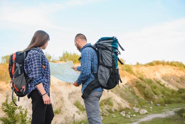 Beau couple de voyageurs cherchent moyen sur la carte de localisation en se tenant debout sur une haute colline en journée ensoleillée