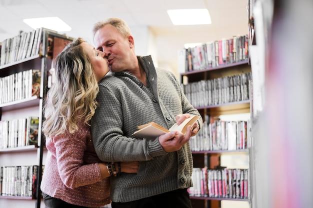 Beau, couples aînés, baisers, dans, bibliothèque