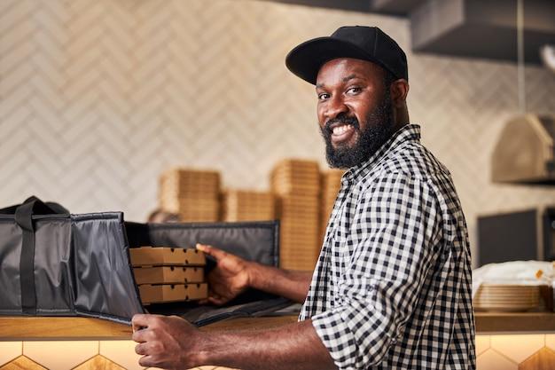 Beau coursier masculin regardant la caméra et souriant tout en emballant des boîtes à pizza en carton dans un sac thermique isolé