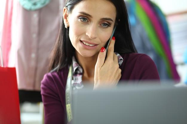 Un beau créateur de mode prend les commandes en ligne par téléphone