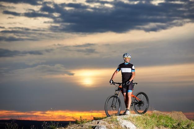 Beau cycliste masculin souriant et debout avec vélo sur rock hill