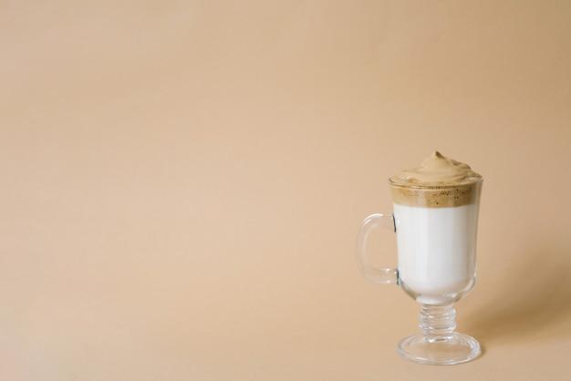 Beau dalgon boit du café avec de la mousse dans une tasse transparente sur fond beige avec copie de l'espace
