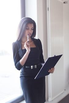 Beau dame d'affaires jeune en noir forte suite tenir la tablette