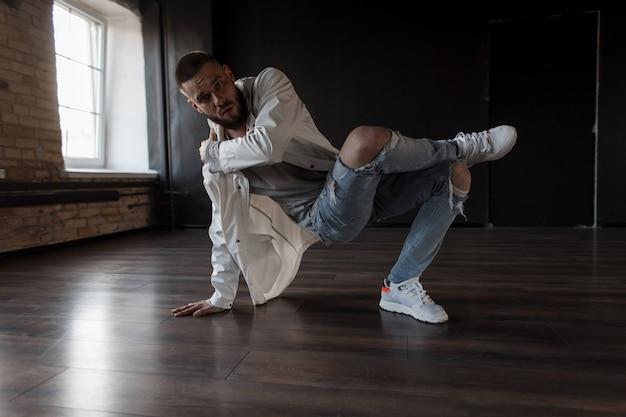 Beau danseur à la mode. l'homme dans une veste blanche avec un jean déchiré noir effectue dans un studio de danse sombre