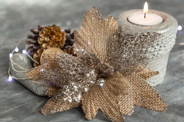 Beau décor de noël dans des tons argent doré, une fleur inhabituelle de pommes de pin et une bougie allumée styl...