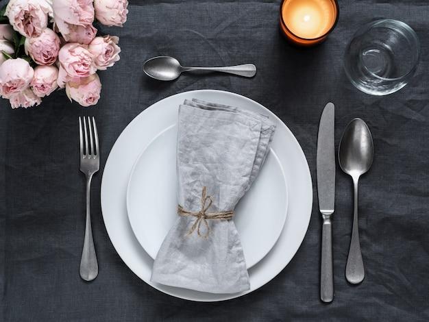 Beau décor de table avec des roses en spray rose et une bougie sur une nappe en lin gris.