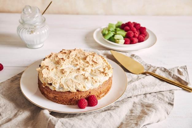 Beau et délicieux gâteau aux framboises et à la rhubarbe avec des ingrédients sur une table