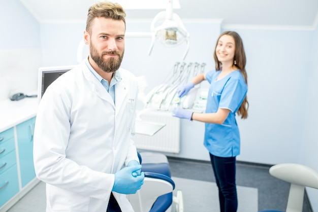 Beau dentiste avec une jeune assistante en uniforme se préparant au travail au cabinet dentaire